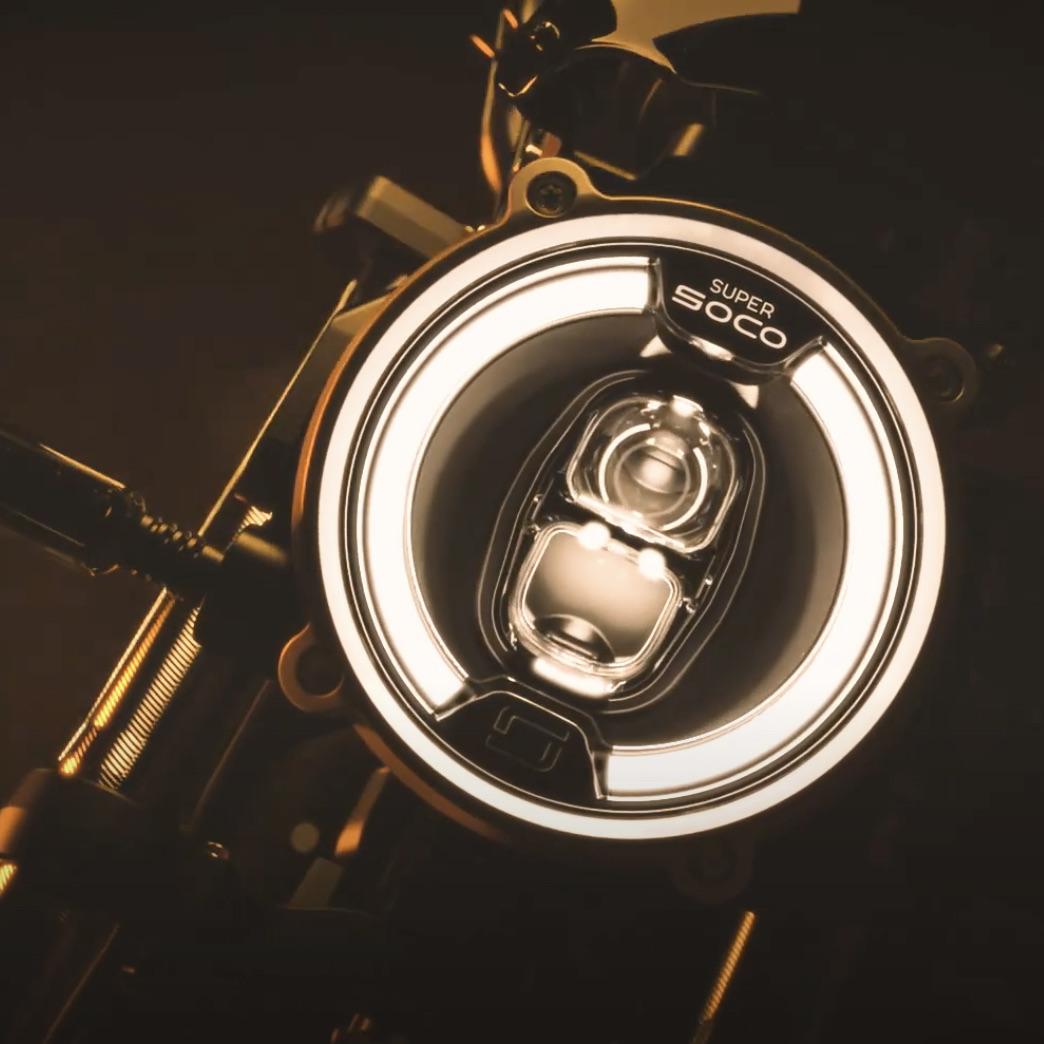 """Nie tak dawno pisałem o elektrycznej premierze, którą szykuje dla nas popularne Super Soco. Wszyscy klienci oraz fani tej chińskiej marki premium spodziewali się miejskiego motocykla. Okazuje się, że premierę będą miały w tym roku co najmniej dwa pojazdy tej firmy. Teraz dowiadujemy się o modelu inspirowanym klasycznymi, retro motocyklami - Super Soco TC Wanderer. W poprzednim artykule, który znajdziecie pod tym linkiem, przekazałem Wam szczątkowe informacje, jakie przekazał producent, oraz to, co z krótkiego filmu można wywnioskować. Chociaż, bardziej dociekliwe osoby sugerowały, że Super Soco zaprezentuje więcej niż tylko jeden nowy model, nie było tak naprawdę powodów, by odnieść takie wrażenie. Producent postanowił jednak oficjalnie podgrzać atmosferę przed premierą i pokazał na, krótkim filmie nowy model - Super Soco TC Wanderer. Super Soco TC Wanderer dysponuje 200 km zasięgu? Tak jak w przypadku modelu TS Street Hunter, tak również i teraz nie dostajemy żadnych szczegółów na temat nowego motocykla. Wszystko, co wiemy, opiera się na obserwacjach i wnioskach, jakie nasuwają się po obejrzeniu krótkiego filmu. Podobnie jak w poprzednim wypadku widzimy sylwetkę pojazdu, który odsłania nowe elementy stylistyczne oraz wyświetlacz, który zdradza pewną ciekawostkę. Stylistykę nowego modelu ocenicie sami, pewnie się jednak zgodzimy, gdy napiszę, że nowy TC Wanderer nawiązuje do klimatu retro. Oszczędny, surowy styl nawiązujący do motocykli z przeszłości - wysoko zarysowany bak, surowa kanapa czy opony z agresywnym, terenowym bieżnikiem - to cechy, które nadają Super Soco charakteru. Oczywiście wszystko to w klimacie """"neoretro"""". Producent nadal oferuje nowoczesne oświetlenie LED, a większość bocznych paneli wykonano z materiałów sztucznych. Mimo to osiągnięto niezwykły efekt. To, co robi jednak największe wrażenie, to wyświetlacz i informacje, które zdradza. W przypadku poprzedniego modelu sugerował on maksymalną prędkość oraz dwa niezależne akumulatory. Teraz Super Soc"""